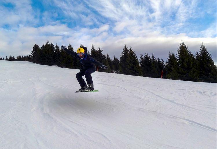 Full length of man skateboarding on snowy mountain against sky
