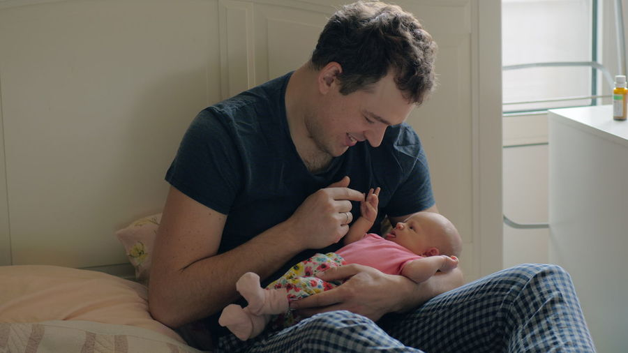 Father with baby on bed