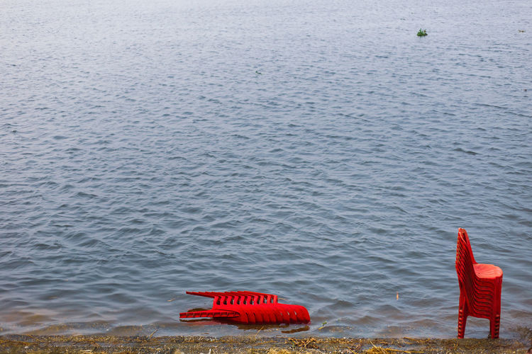 Red floating on sea shore