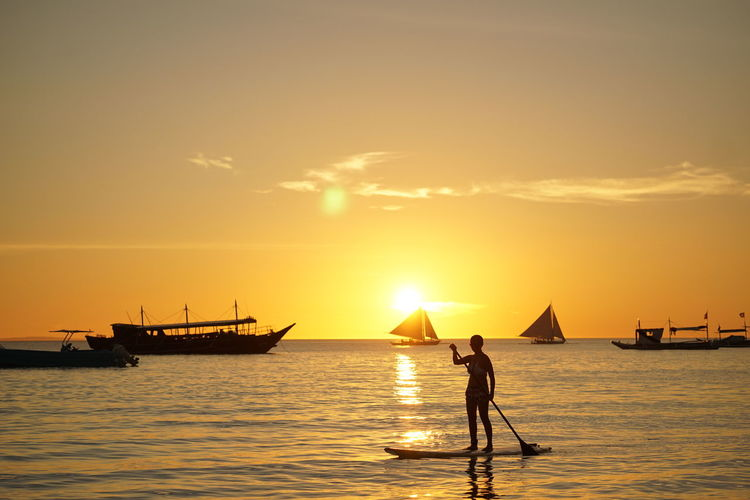 Silhouette woman paddleboarding in sea against sky during sunset