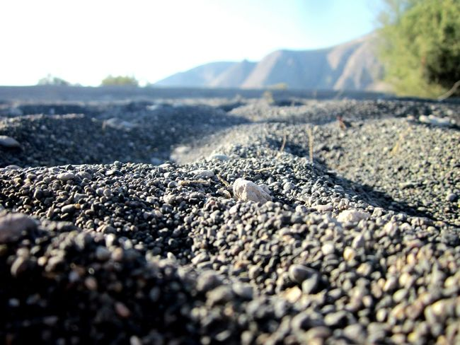 🇬🇷Black Beach Perissa Santorini Macro Photography Sand Closeup In Nature Selective Focus Surface Level Mountain Beauty In Nature Mountain Range Greek Summer Low Angle View Stones And Pebbles Focus On Foreground Mountains In Background Greece At The Beach Life Is A Beach