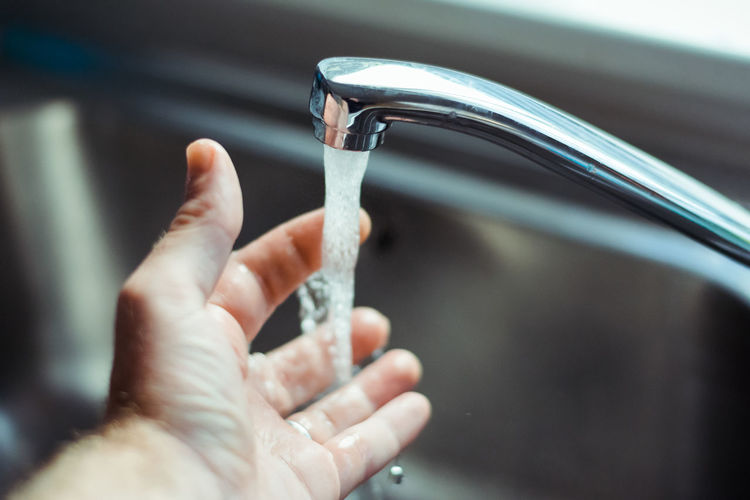 Cropped image of person washing hand in faucet