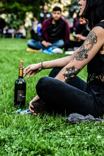 Adult Casual Clothing Day Field Focus On Foreground Grass Green Color Group Of People Hairstyle Incidental People Leisure Activity Lifestyles Nature Outdoors People Plant Real People Sitting Tattoo Women Young Adult Young Women