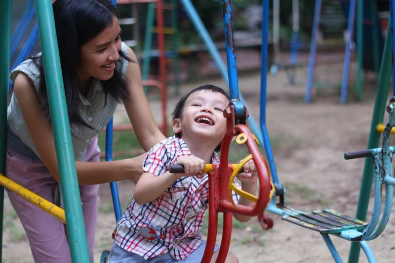 Mother With Cheerful Son Sitting On Play Equipment At Playground