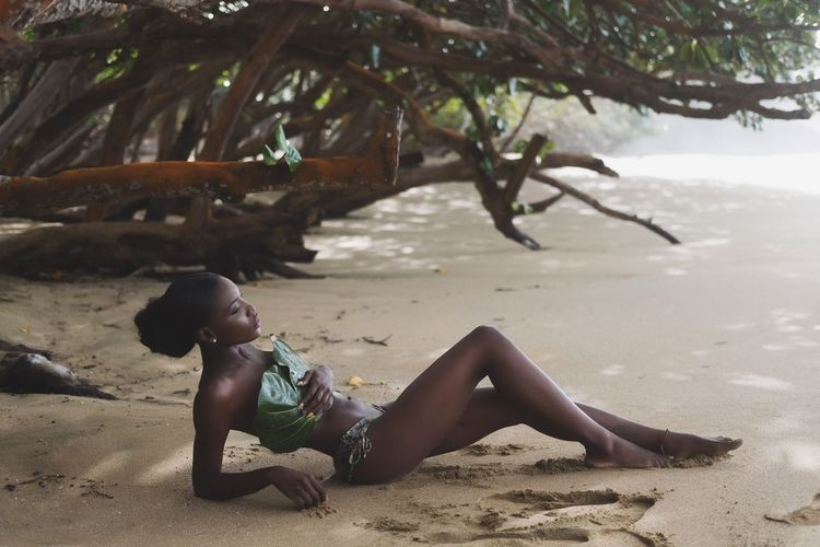 Close-up of young woman lying on sand at beach