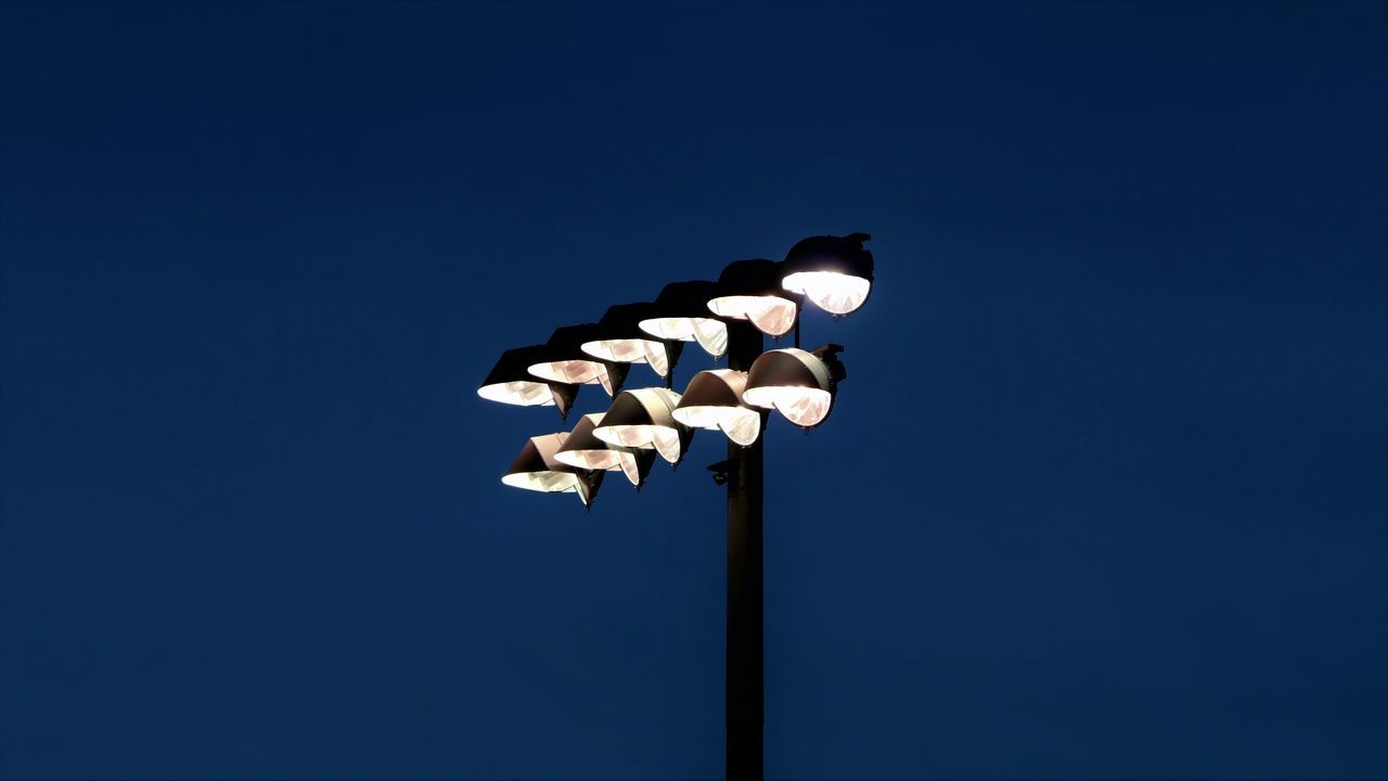 Low angle view of illuminated floodlight at night