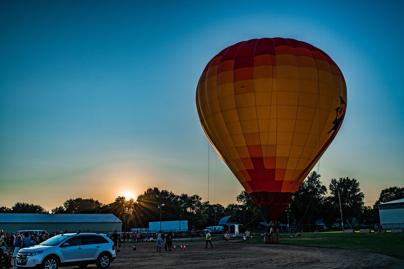 Transportation Mode Of Transportation Sky Sunset Motor Vehicle Hot Air Balloon Balloon Car Land Vehicle Nature Air Vehicle Incidental People Adventure Tree Orange Color Travel Blue Beauty In Nature Clear Sky Multi Colored Outdoors Ballooning Festival