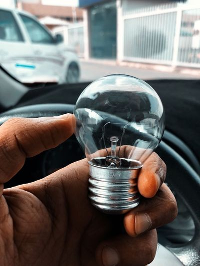 Cropped Hand Holding Light Bulb In Car