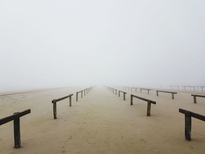 Wooden pier on sea against sky during foggy weather