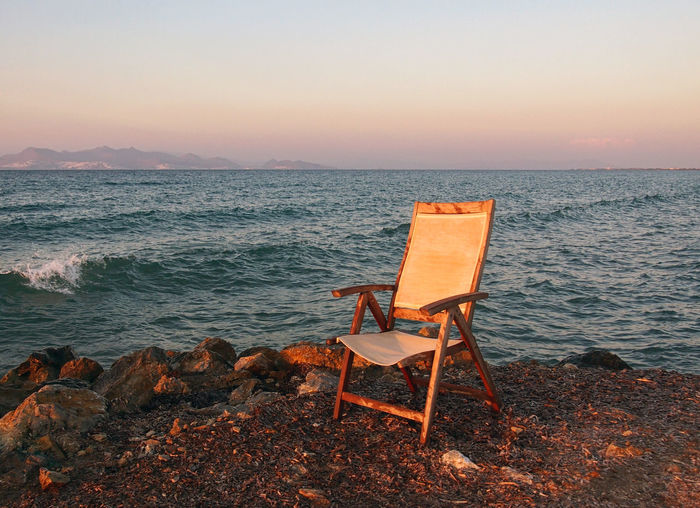 empty chair by the sea at sunset in kos greece Chair Twilight Absence Beach Beauty In Nature Chair Empty Empty Road Horizon Horizon Over Water Land Nature No People Orange Color Rock Scenics - Nature Sea Seat Sky Sunset Sunsets Tranquil Scene Tranquility Water