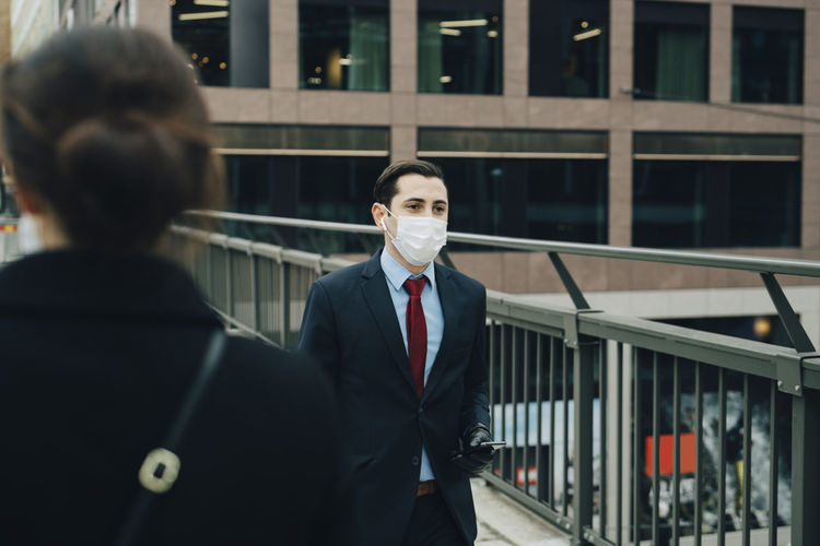 Portrait of young man standing at office building