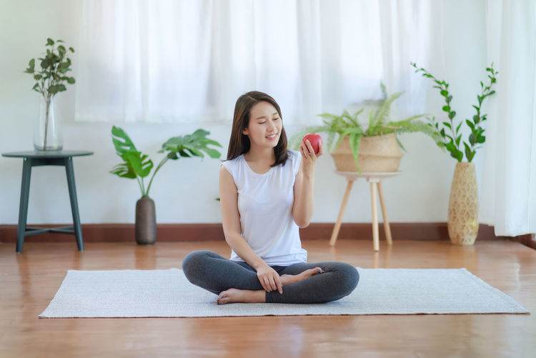 Full length of woman sitting on wooden floor at home