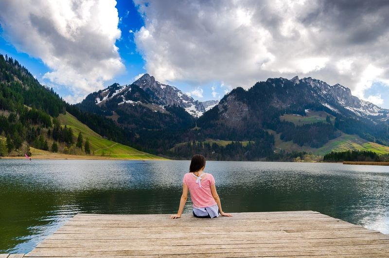Rear view of girl by lake against cloudy sky