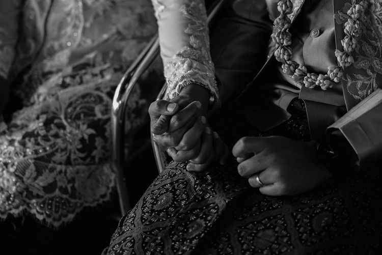 Midsection of bride holding groom hand during wedding ceremony