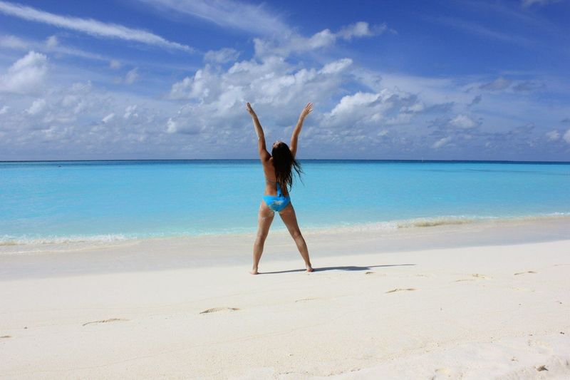 Full Length Rear View Of Woman With Arms Raised Standing At Beach Against Sky