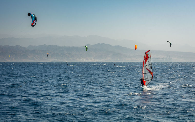 Man paragliding over sea against clear sky