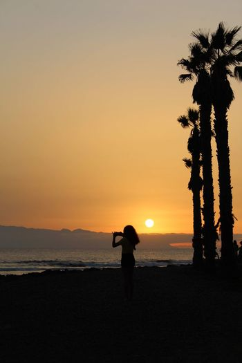 Silhouette woman standing at beach against sky during sunset
