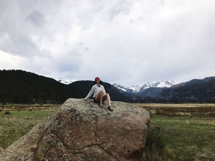 Young woman sitting on rock against cloudy sky