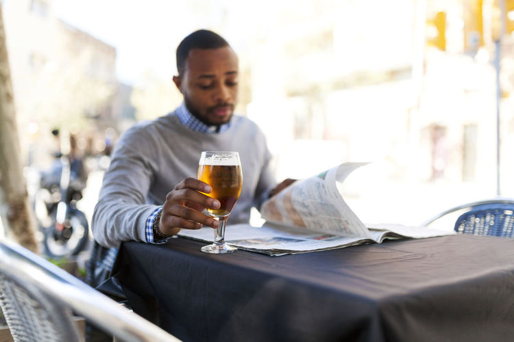 Full length of a young man drinking glass on table