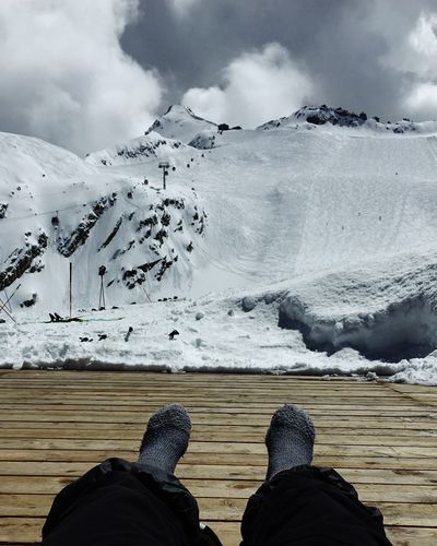 Low section of person on boardwalk against snowcapped mountain