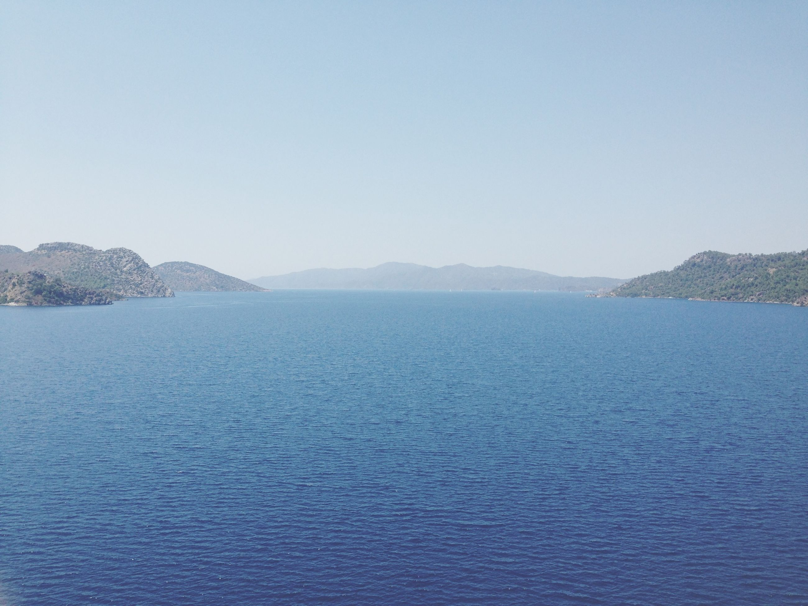 water, clear sky, tranquil scene, copy space, scenics, tranquility, sea, beauty in nature, mountain, waterfront, nature, blue, idyllic, rippled, mountain range, outdoors, day, no people, remote, non-urban scene