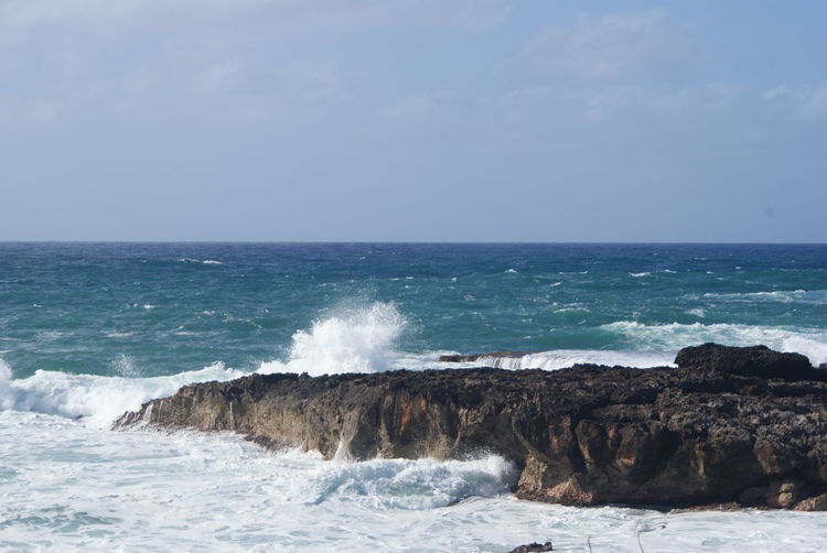 Waves splashing on rocks at beach against sky