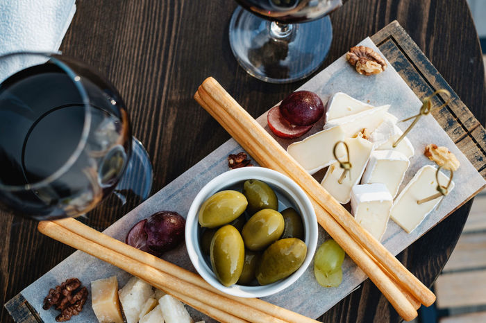 Still life shot of red wine and snacks. Top view food Olive Red Wine Cheese Directly Above Drink Drinking Glass Food Food And Drink Freshness Fruit Gastronomy Glass Healthy Eating High Angle View Household Equipment No People Olive Red Wine Refreshment Table Top View Of Food Wood - Material Wooden Spoon