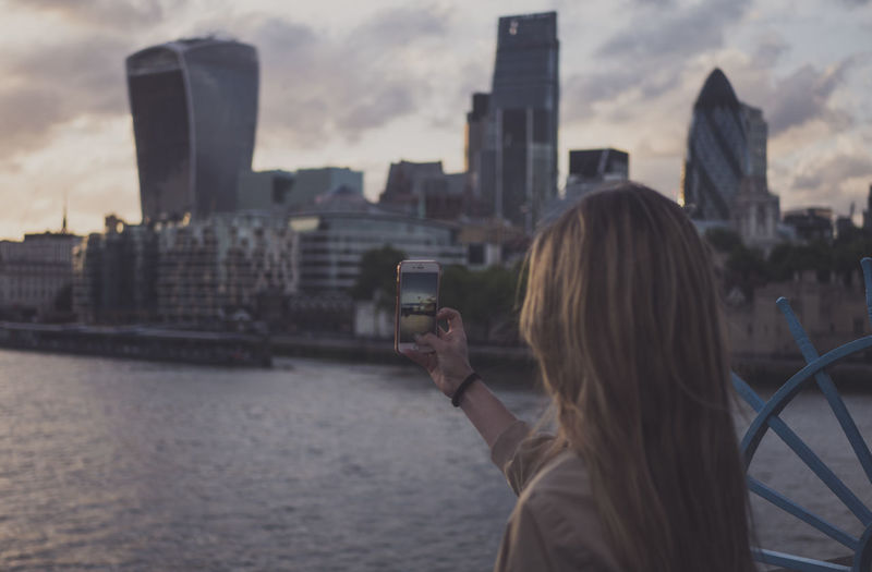 Woman photographing buildings and thames river at dusk
