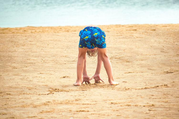 Full length of boy relaxing on beach