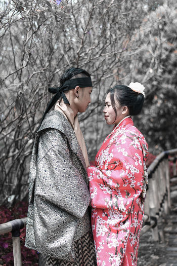 Couple In Traditional Clothing Standing At Forest