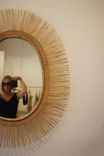 Reflection of woman holding camera in mirror