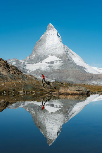 Don't forget to follow me at http://www.instagram.com/simonmigaj and check out my website http://simonmigaj.com Lost In The Landscape Matterhorn  Red Reflection Travel Zermatt Adventure Blue Clear Sky Cold Temperature Day Lake Leisure Activity Lifestyles Mountain Mountain Range Nature One Person Outdoors Real People Scenics Snow Snowcapped Mountain Tranquility Water