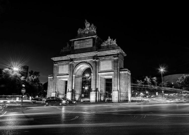 Light Trails On Illuminated Street By Puerta De Toledo Against Sky At Night