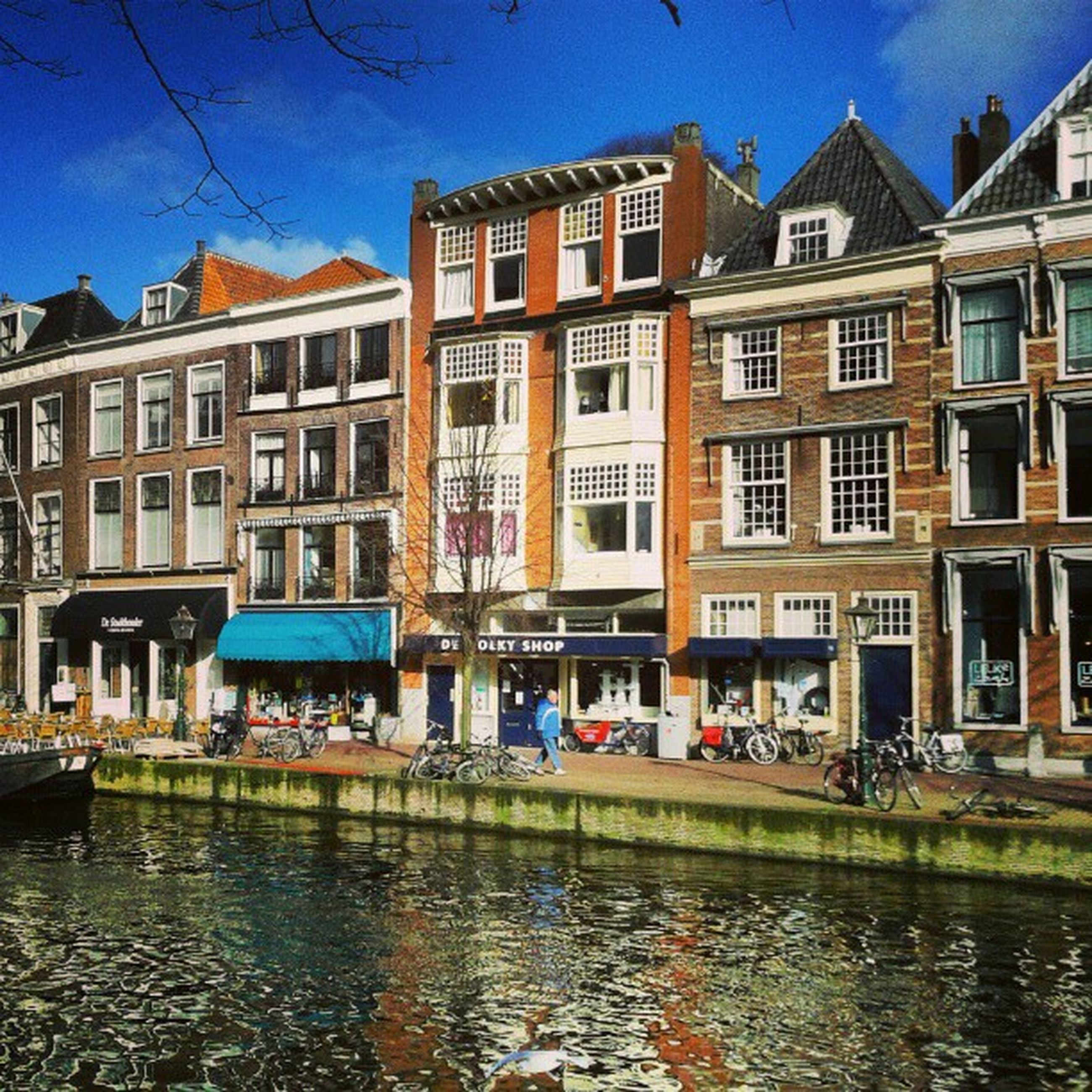 architecture, building exterior, built structure, water, canal, waterfront, residential building, residential structure, reflection, building, city, blue, window, sky, incidental people, house, old town, city life, residential district, facade