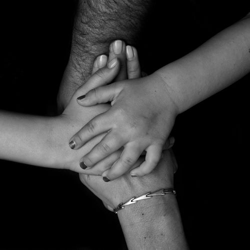 Cropped image of family stacking hands over black background