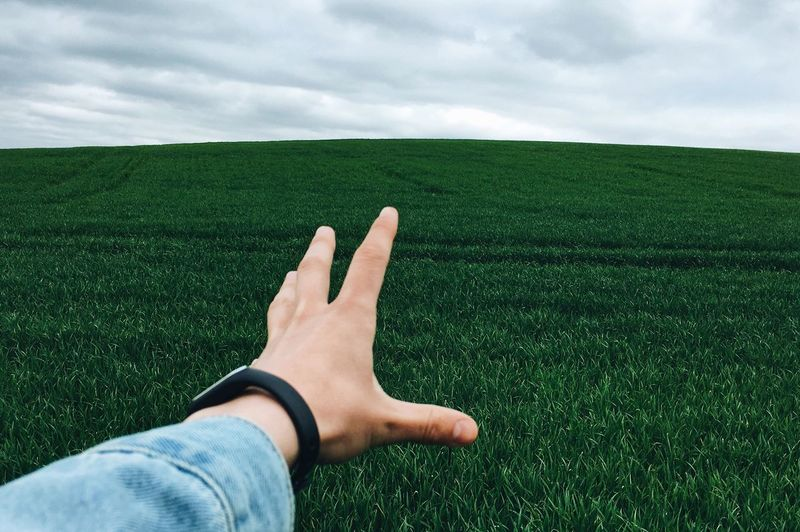 Cropped hand of person reaching sky over grassy field