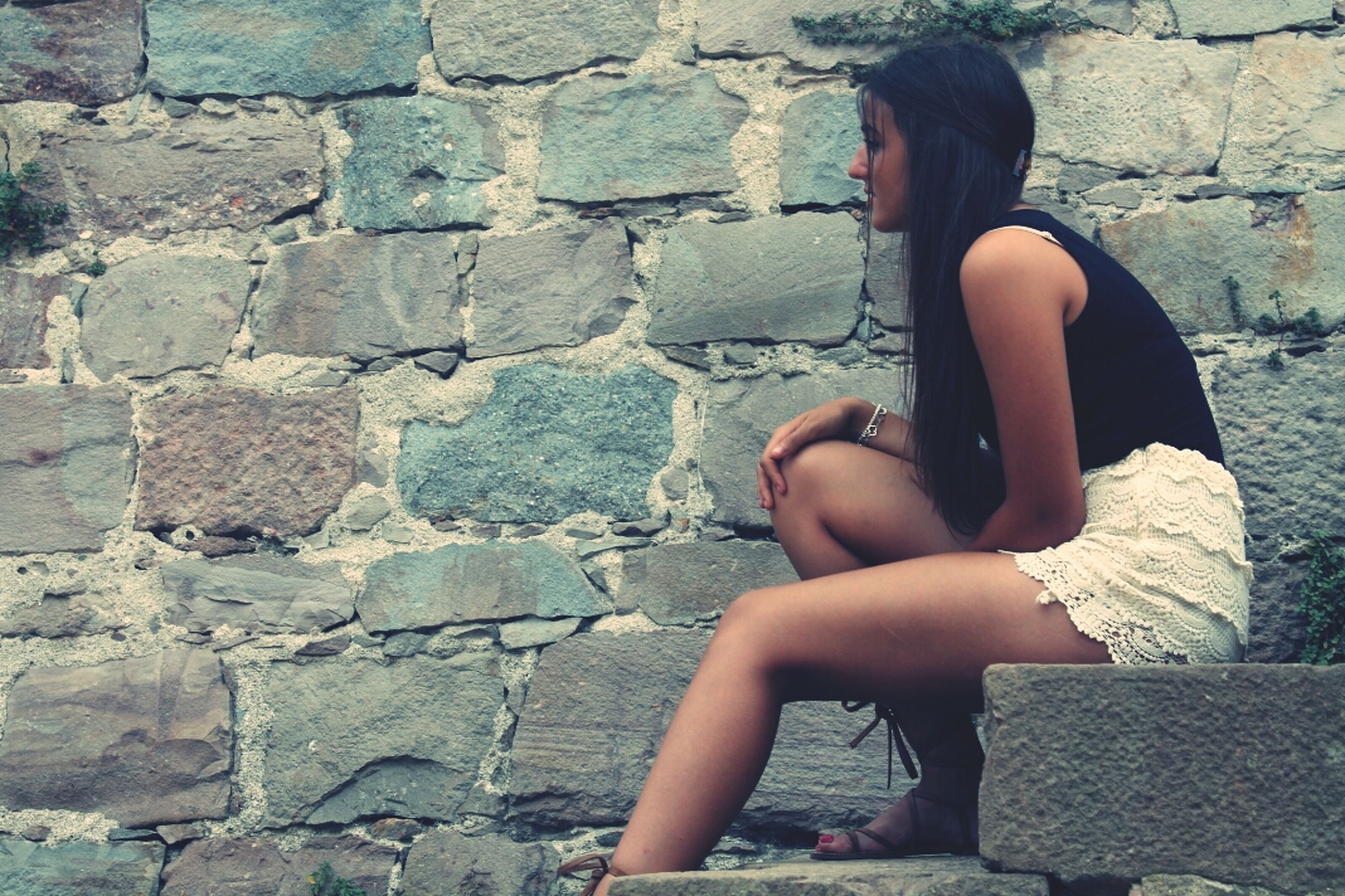 lifestyles, young adult, standing, young women, leisure activity, stone wall, wall - building feature, brick wall, casual clothing, person, full length, long hair, side view, three quarter length, front view, wall