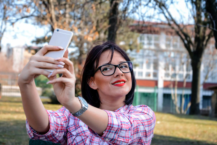 Woman taking selfie from mobile phone against trees at park
