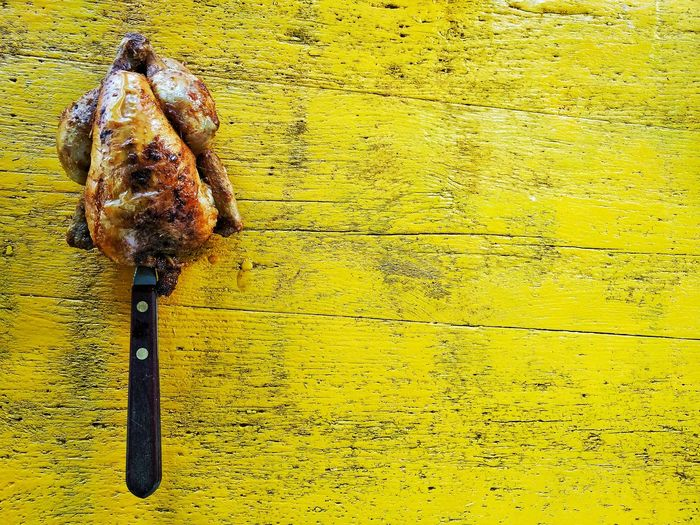 Directly Above View Of Knife In Grilled Chicken On Yellow Table