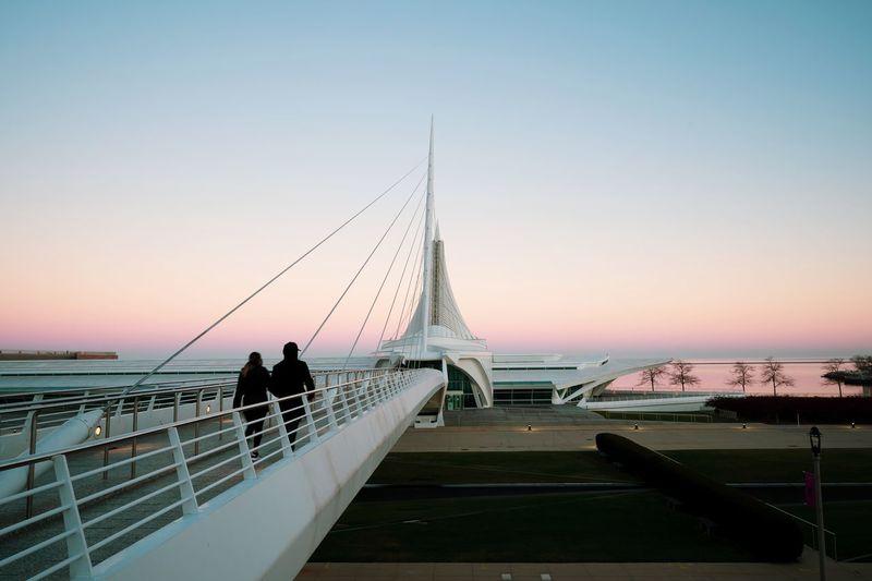 People on bridge over sea against sky during sunset