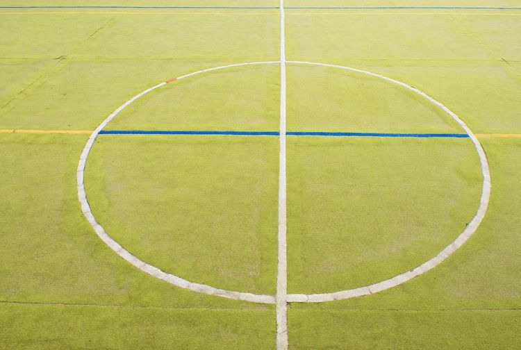 Circle in middle of court. handball playground, light green surface and white blue bounds lines.
