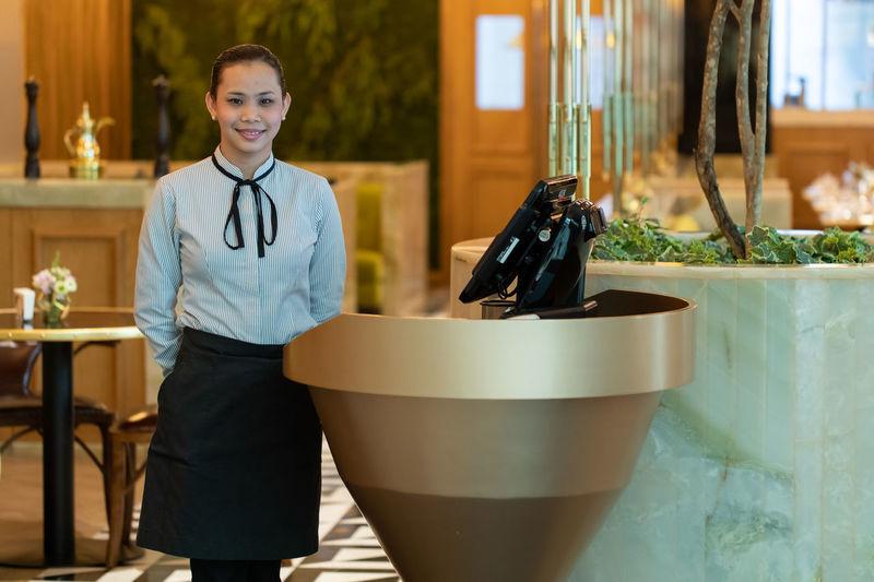 Portrait of receptionist standing in hotel