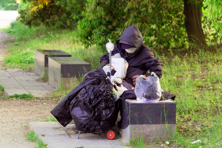 Person holding garbage bag while sitting on bench at park
