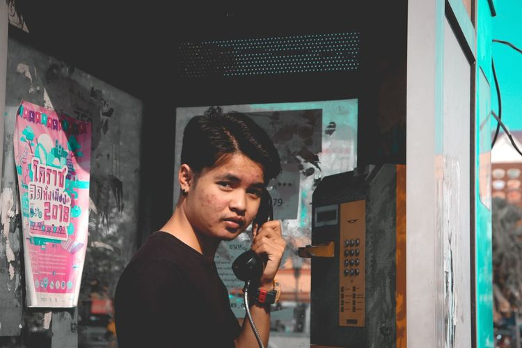 Portrait of young man using pay phone