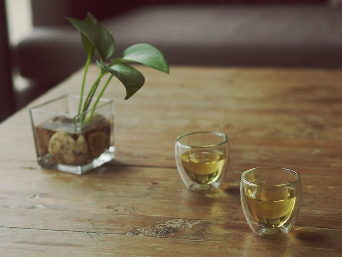 Tea In Glass By Leaves On Wooden Table