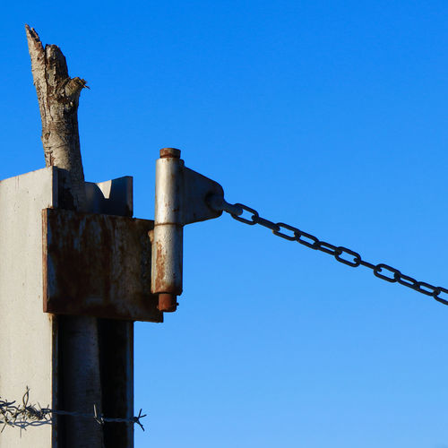 Low angle view of rusty chain against blue sky