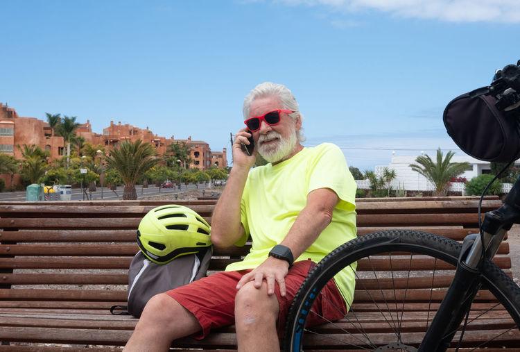 Smiling senior man using phone while sitting by bicycle on bench