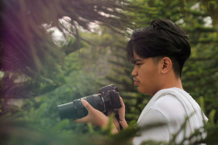 Side view of young man photographing in forest