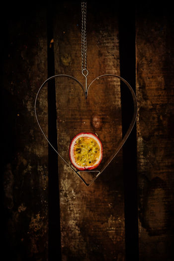Passion fruit in heart shaped metal hanger Close-up Container Crate Fruit Hanging Heart Shape Metal Old-fashioned Passionfruit Red Still Life Wood