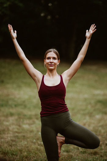 Young woman with arms raised on field